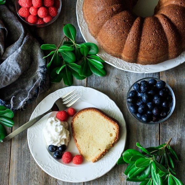 slice of sour cream pound cake on a white plate with fork