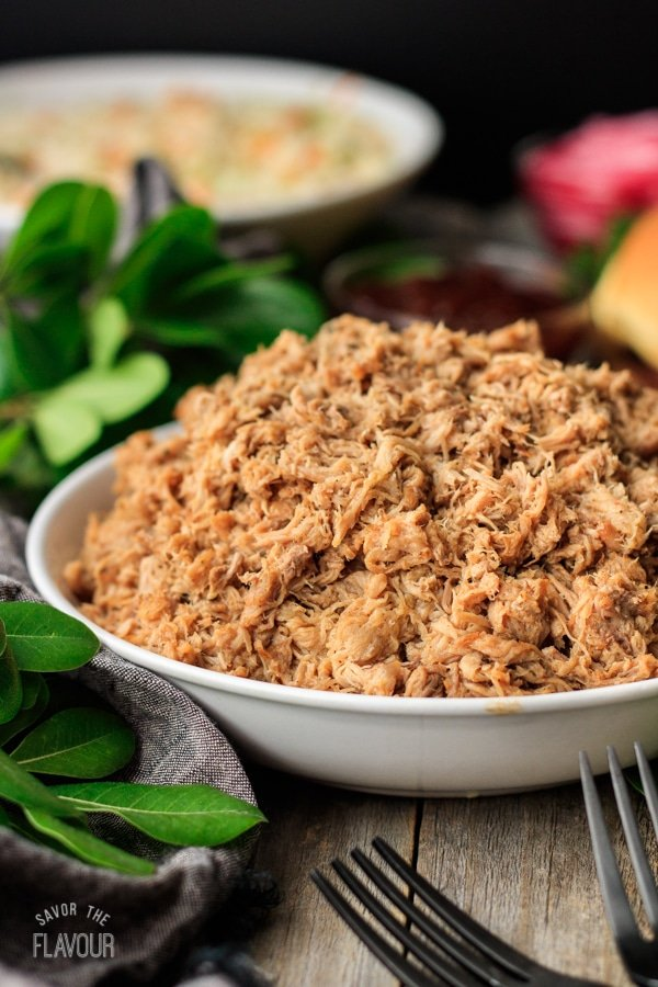 white bowl of pulled pork with two forks, greenery, and gray fabric