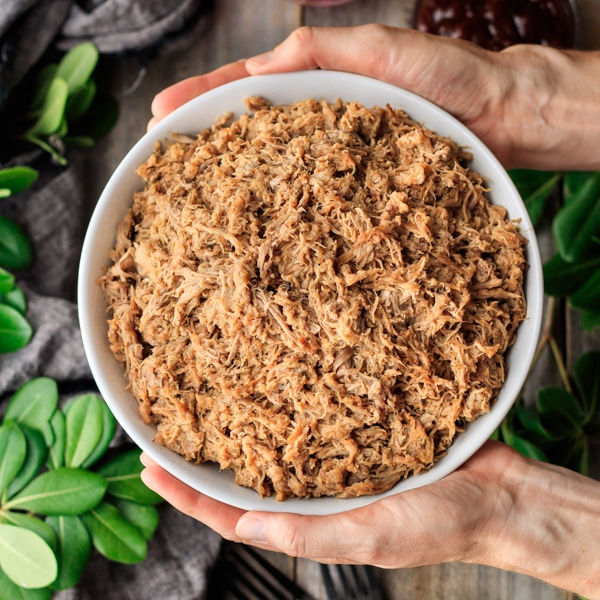 person holding a bowl of pulled pork with greenery in the background