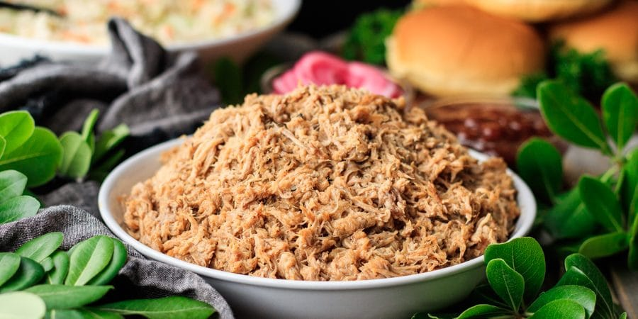 white bowl of pulled pork with pickled onions, coleslaw, and buns in the background