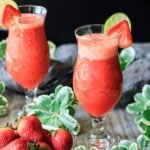 two virgin strawberry daiquiri drinks with a bowl of strawberries, greenery, and gray fabric
