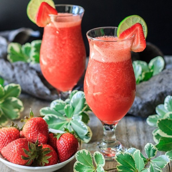 two virgin strawberry daiquiri drinks with a bowl of strawberries and greenery