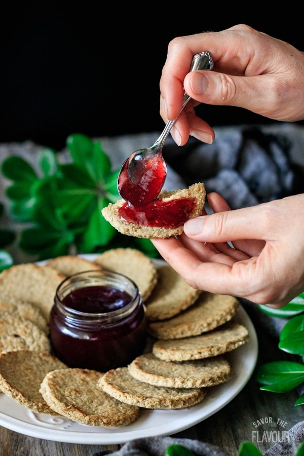 person spreading raspberry jam on an oatcake