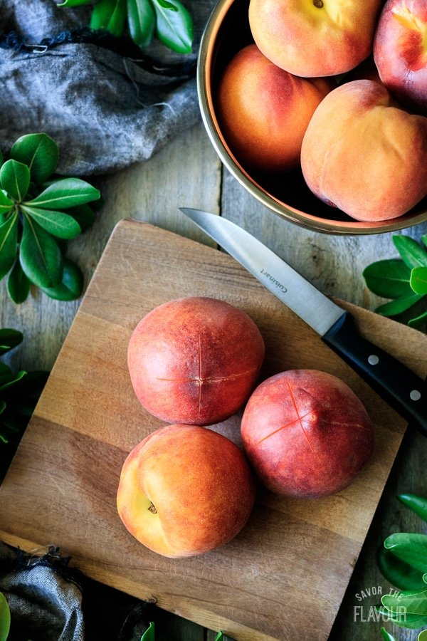 three peaches on a wooden cutting board