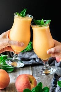 people doing a toast with two virgin peach daiquiri drinks