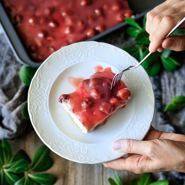 holding a plate with a slice of no bake cherry cheesecake