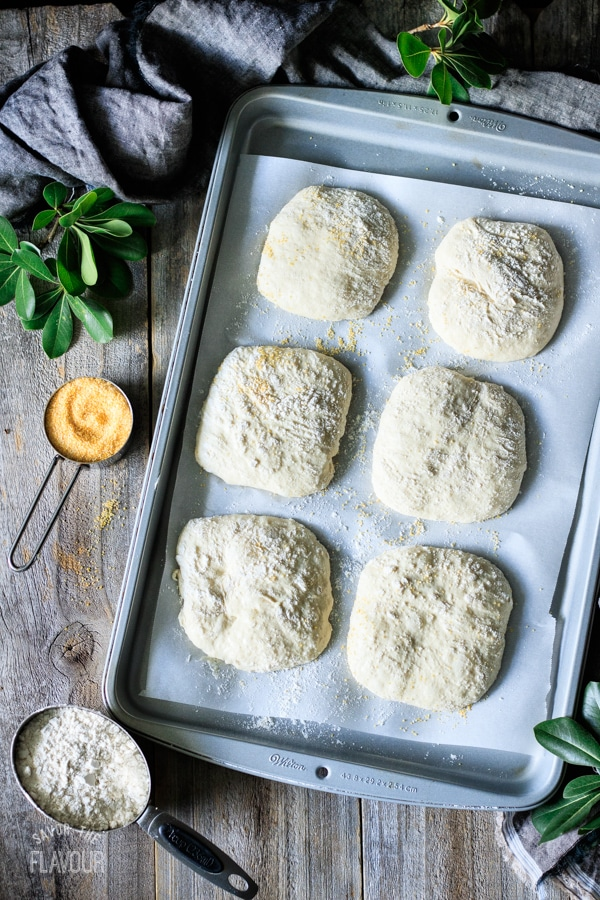 unbaked ciabatta rolls on a cookie sheet