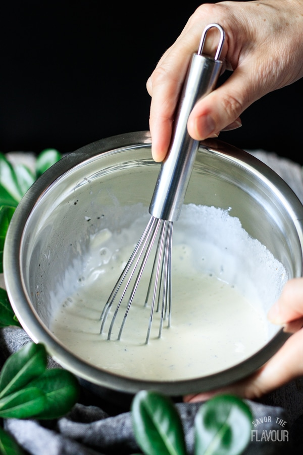 whisking the dressing for pea salad