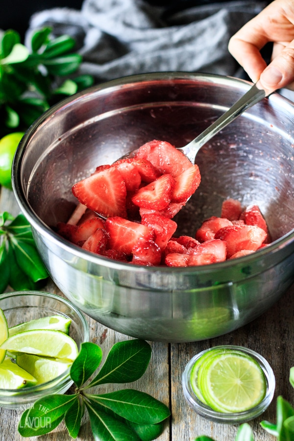 stirring strawberries for non alcoholic strawberry margarita