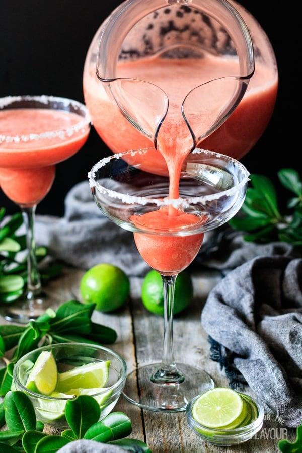 pouring non alcoholic strawberry margarita into the glass