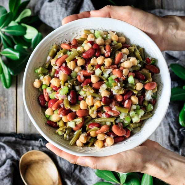 holding a bowl of three bean salad