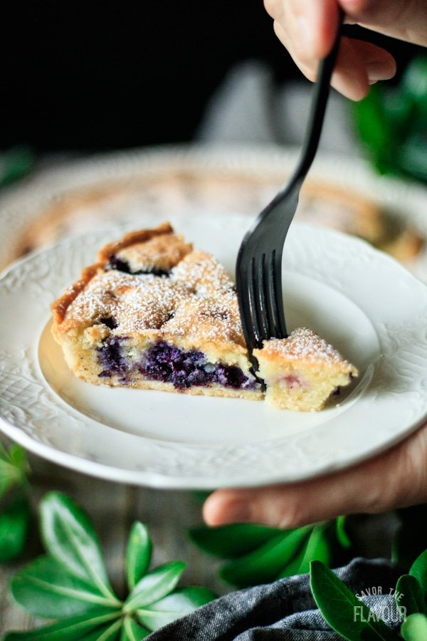 taking a forkful of blueberry frangipane tart