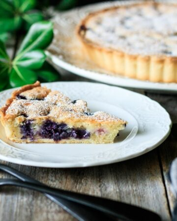 slice of blueberry frangipane tart on a plate with forks
