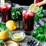 garnishing a glass of blueberry lemonade