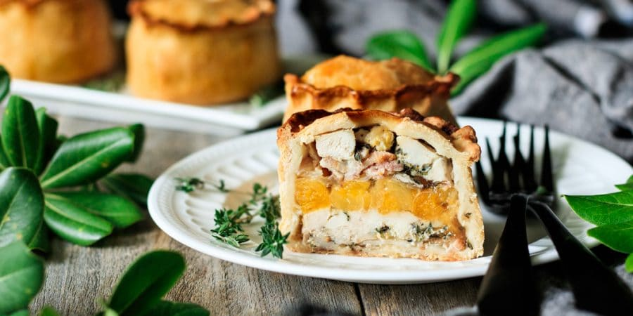 a chicken, bacon, and apricot pie cut in half on a plate
