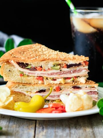 muffaletta sandwich on a plate with a glass of root beer