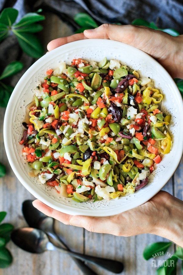 holding a bowl of olive salad for muffaletta