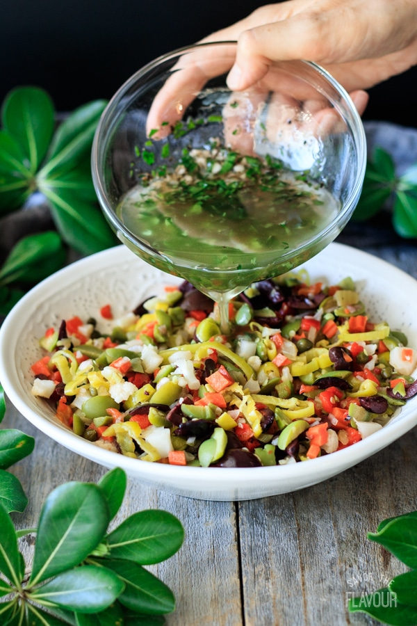 pouring dressing on olive salad for muffaletta