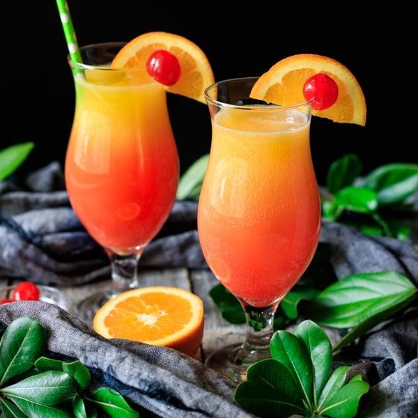 two sweet sunrise drinks with half an orange