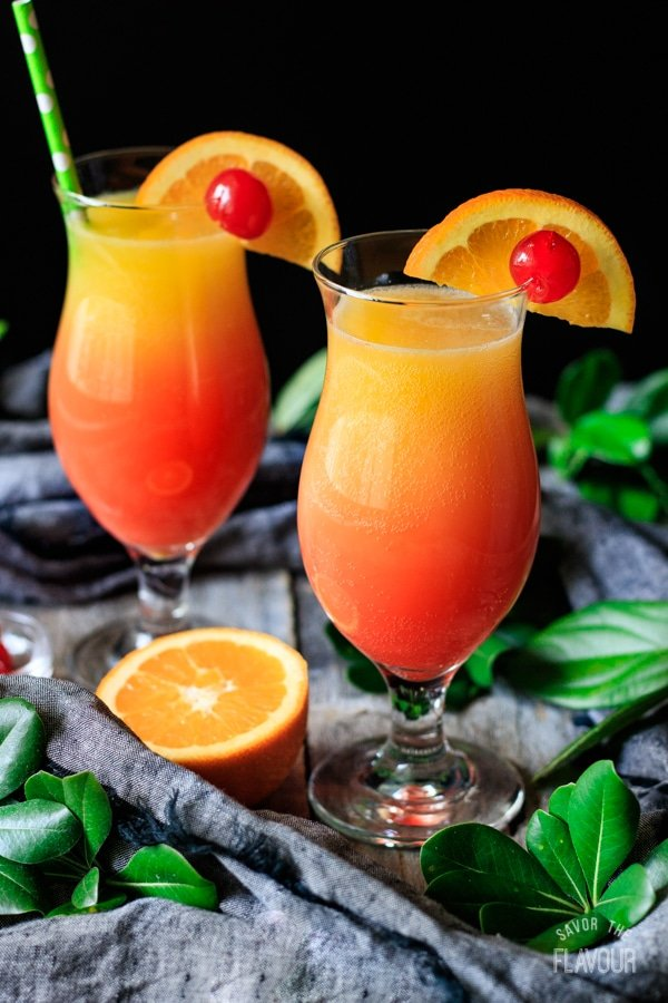 two sweet sunrise drinks with half an orange