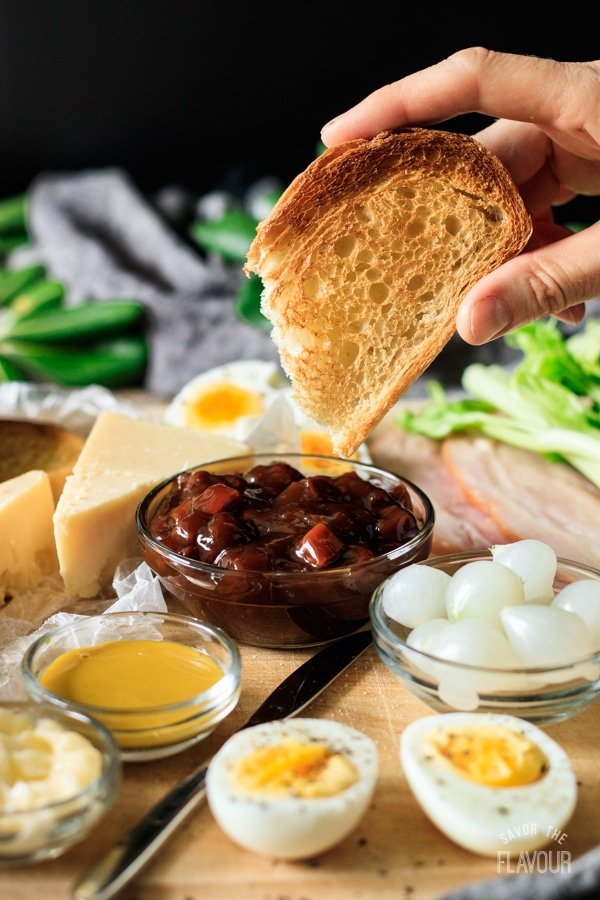dipping bread into a bowl of chutney for ploughman's lunch
