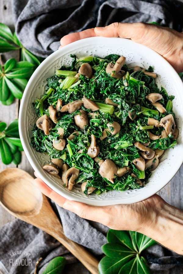 holding a bowl of sautéed kale with mushrooms