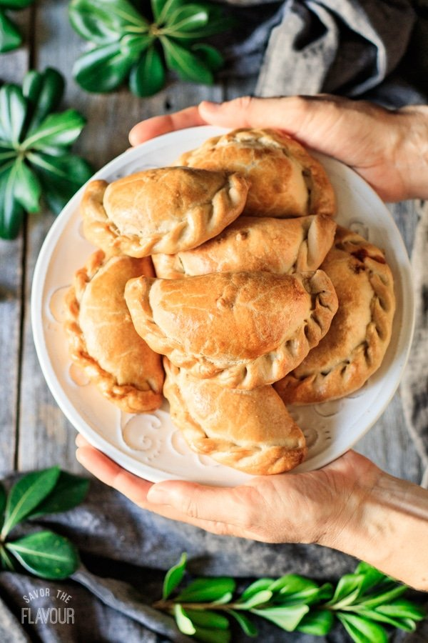 holding a plate of baked chicken empanadas