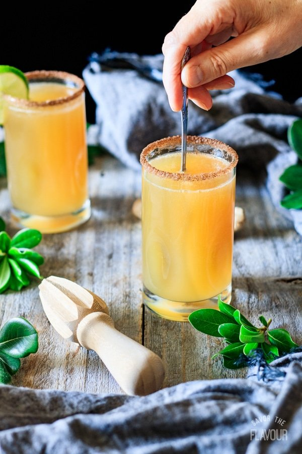 stirring ginger beer mocktail with lime