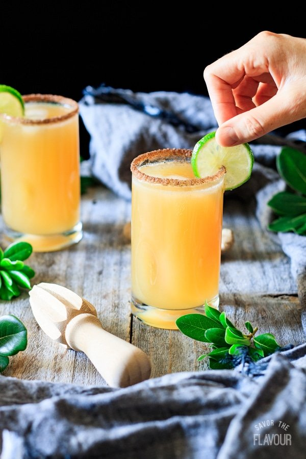 garnishing a ginger beer mocktail with lime