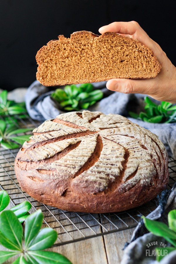 holding a slice of whole wheat molasses bread