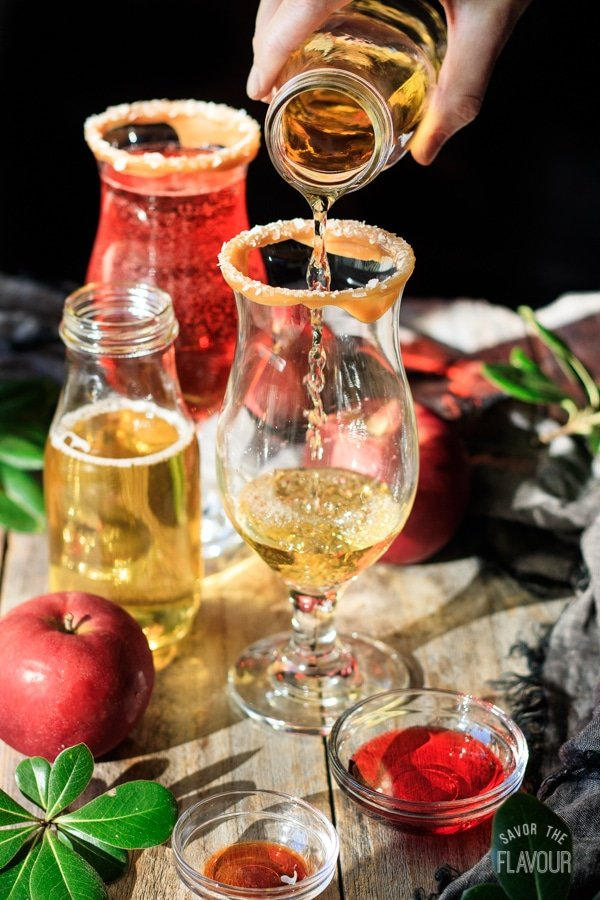 pouring apple juice into a glass for sparkling apple cider mocktail