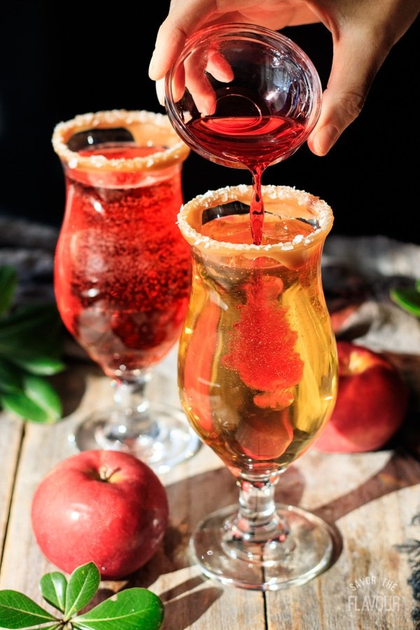 pouring grenadine into a glass for sparkling apple cider mocktail