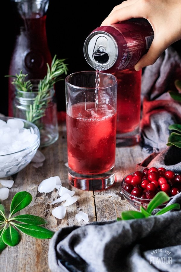 pouring Sprite into a glass for sparkling cranberry mocktail