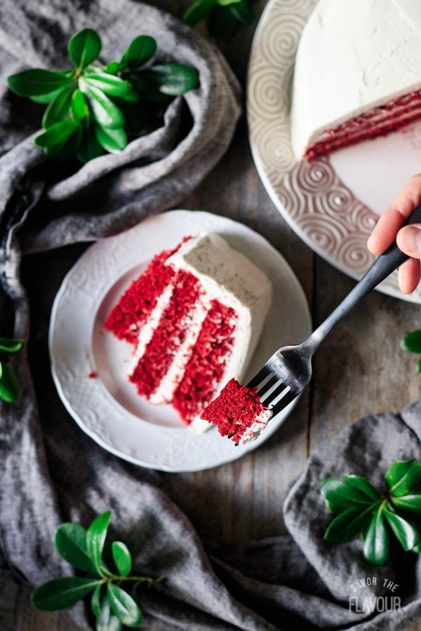 holding a forkful of red velvet cake