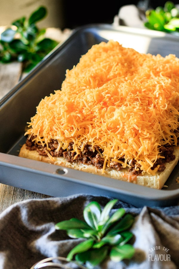 adding the cheese to the sloppy joe sliders