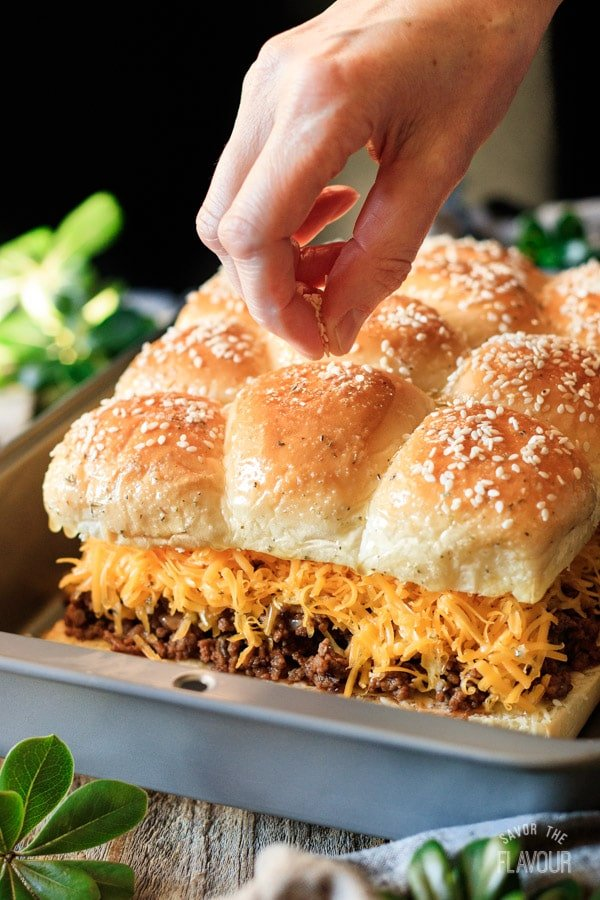 sprinkling sesame seeds on sloppy joe sliders