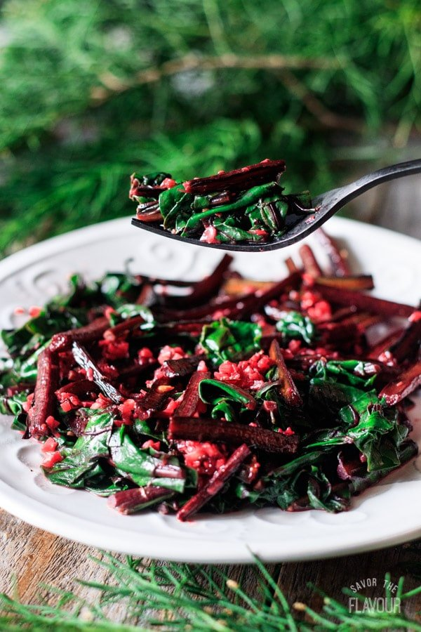 holding a forkful of sautéed beet greens