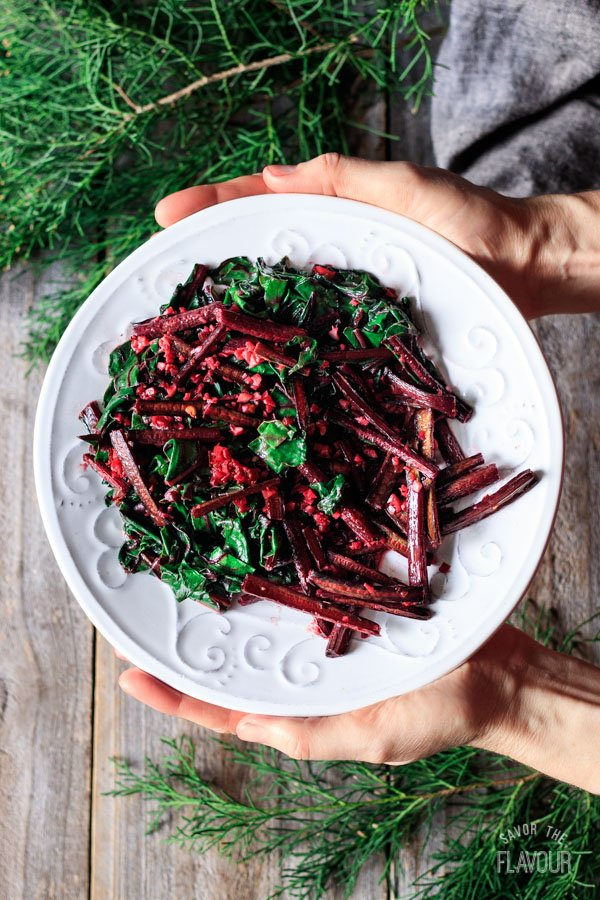 holding a plate of sautéed beet greens