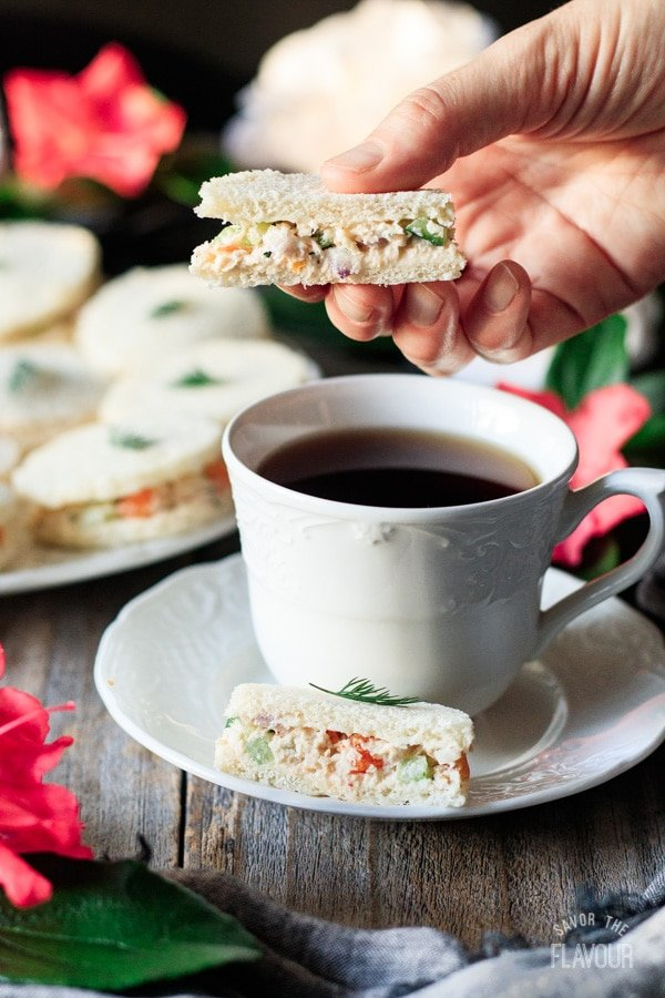 holding half of one of the crab salad sandwiches with a cup of tea