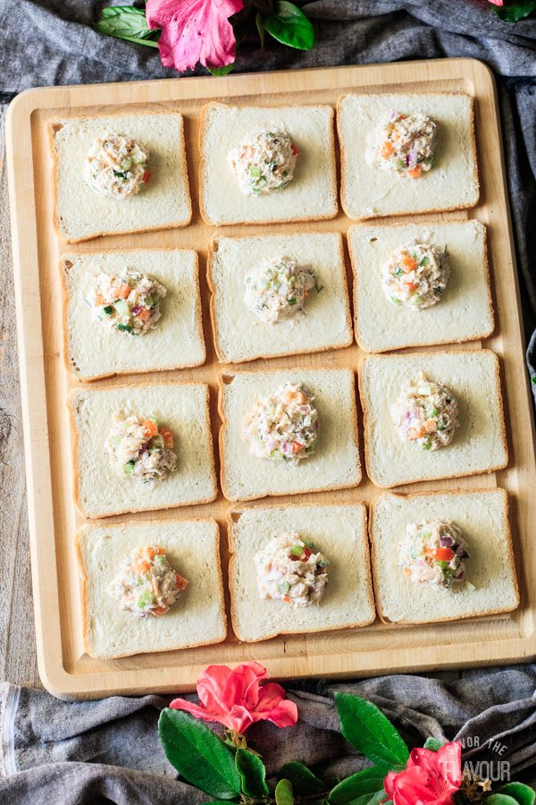 spreading crab salad onto bread for crab salad sandwiches