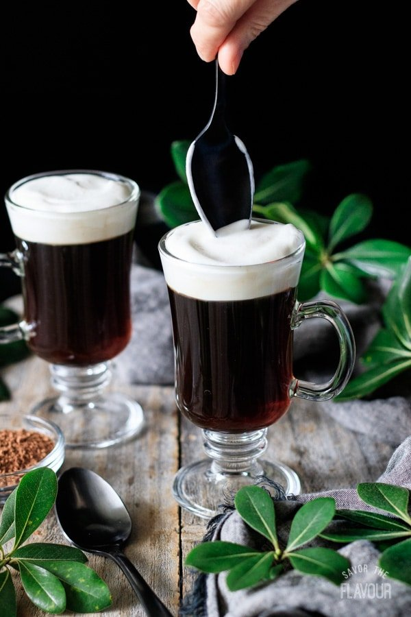spreading whipped cream on top of non alcoholic Irish coffee
