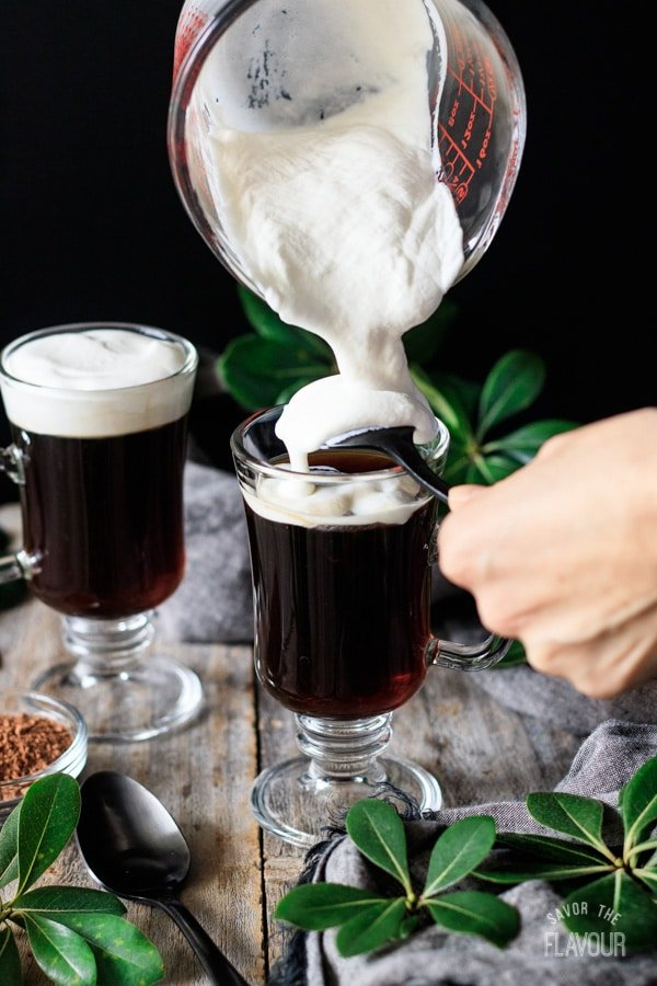 pouring whipped cream on top of non alcoholic Irish coffee