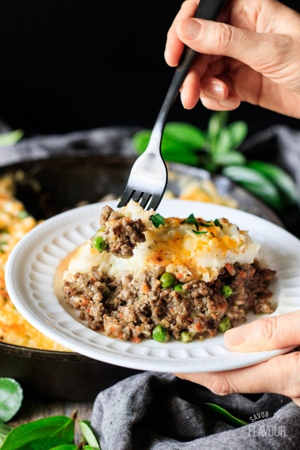 holding a forkful of shepherd's pie