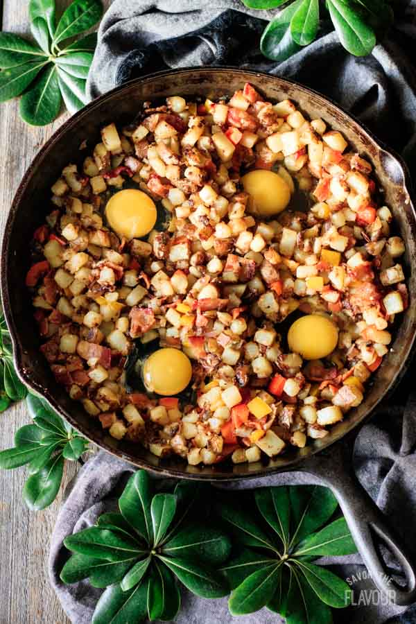adding four eggs to breakfast hash