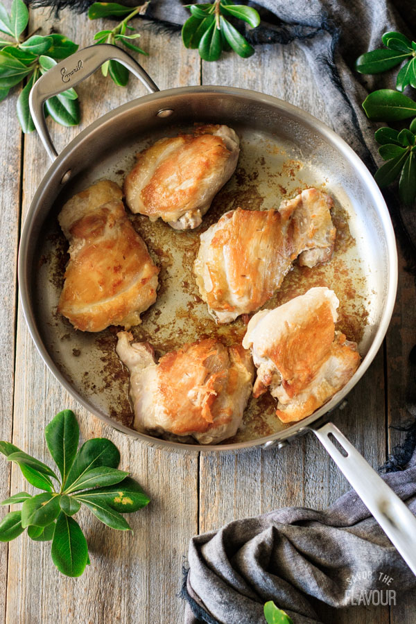 browned chicken in a pan for Asian chicken thighs