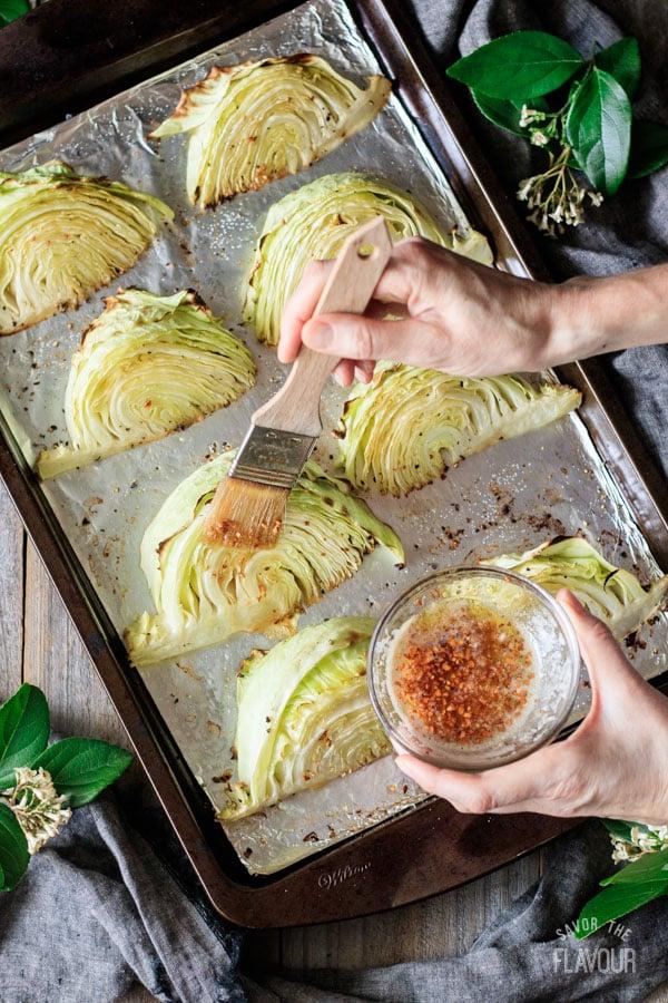 brushing lemon garlic butter on roasted cabbage wedges
