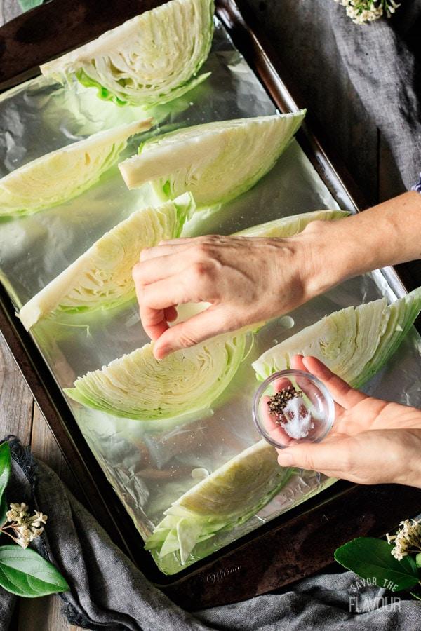 sprinkling salt and pepper on cabbage wedges