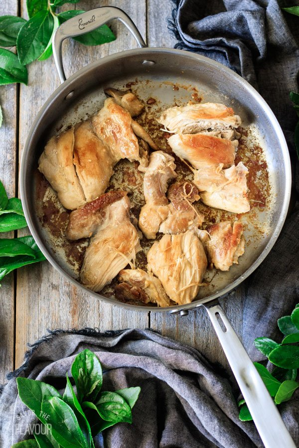 browned chicken thighs in a skillet for chicken and leek pie