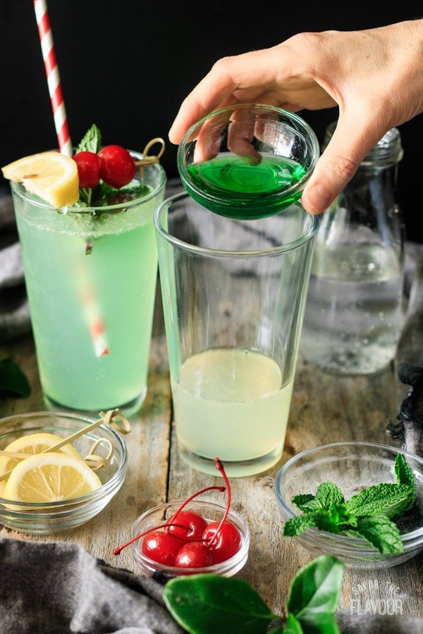 adding homemade creme de menthe to glass for mint julep