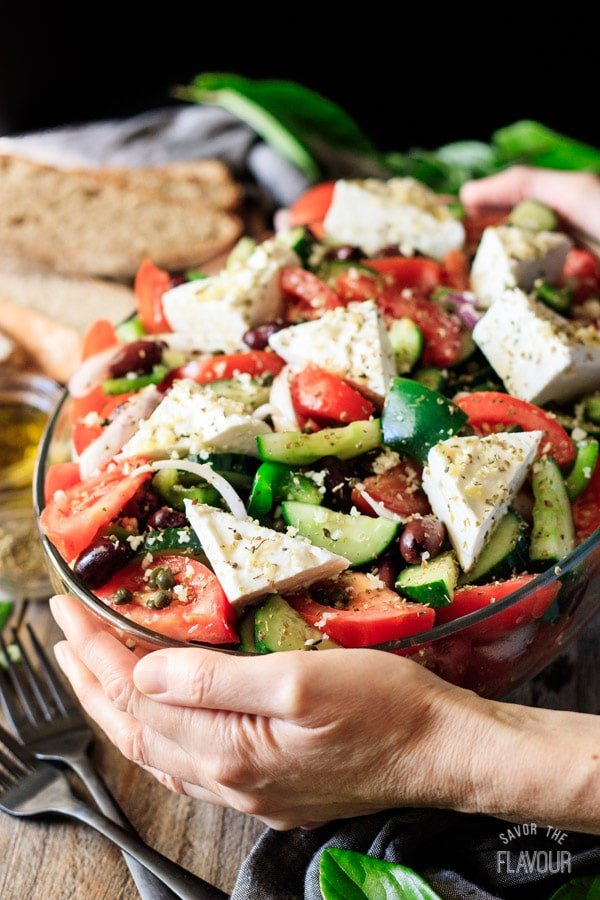 holding a dish of Greek salad